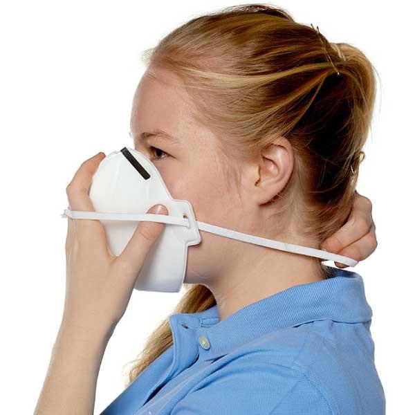 Atemschutzmaske wird ans Gesicht geführt.