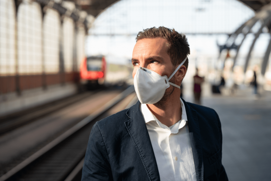 Mann trägt FFP3-Maske am Bahnsteig.