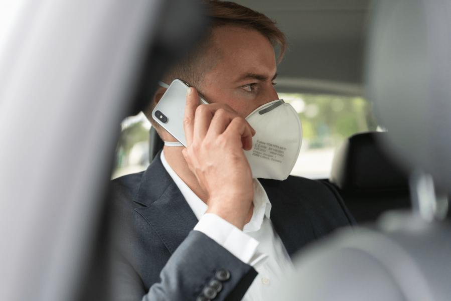 Mann sitzt mit Atemschutzmaske im Taxi und telefoniert.