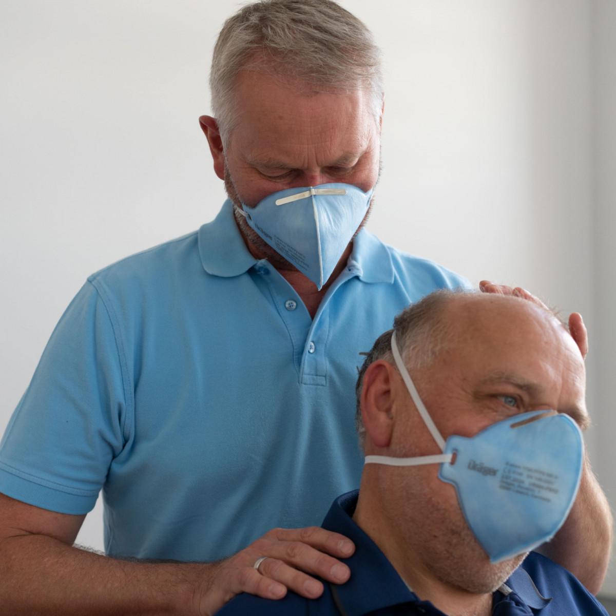 Physiotherapeutische Behandlung mit Atemschutzmaske.