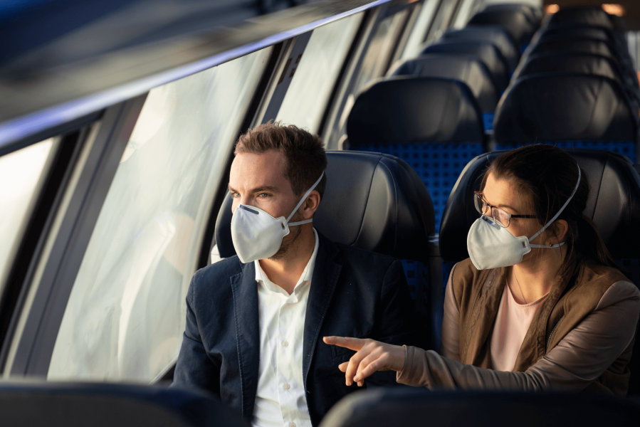 Mann und Frau mit Atemschutzmaske in der Bahn.