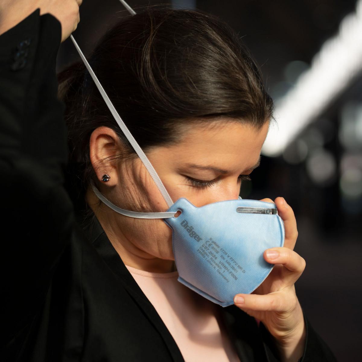 Frau legt Atemschutzmaske an.