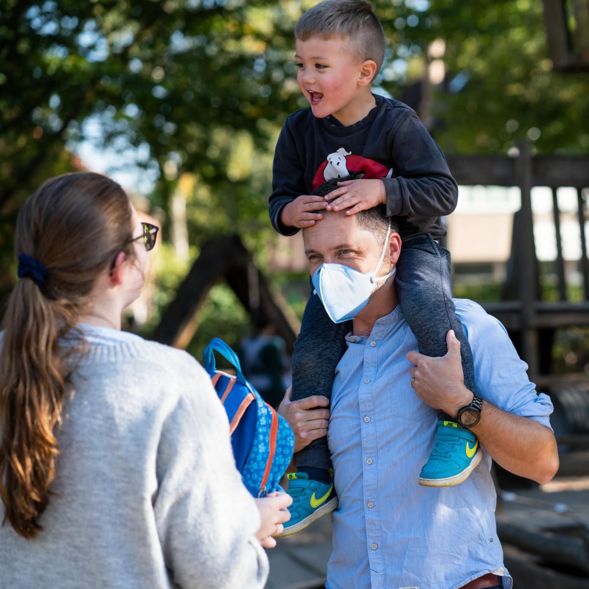 Mann mit Atemschutzmaske trägt Kind auf den Schultern.